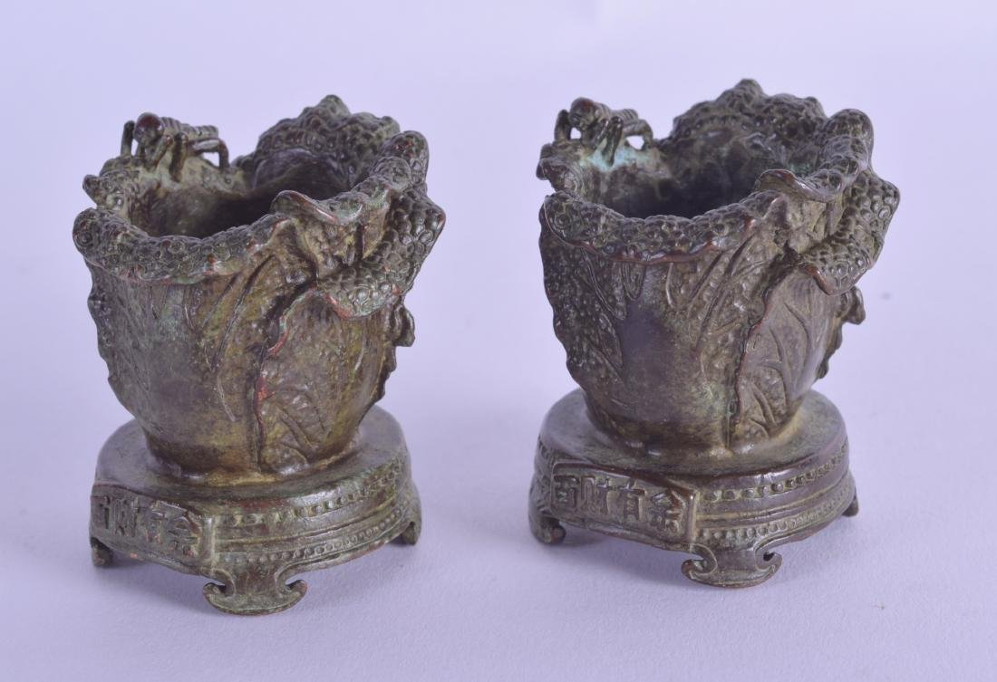 AN UNUSUAL PAIR OF CHINESE BRONE MINIATURE CANDLESTICKS