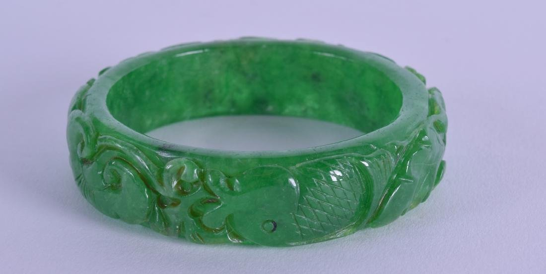 A CHINESE CARVED CHINESE JADE BANGLE. 7 cm diameter.
