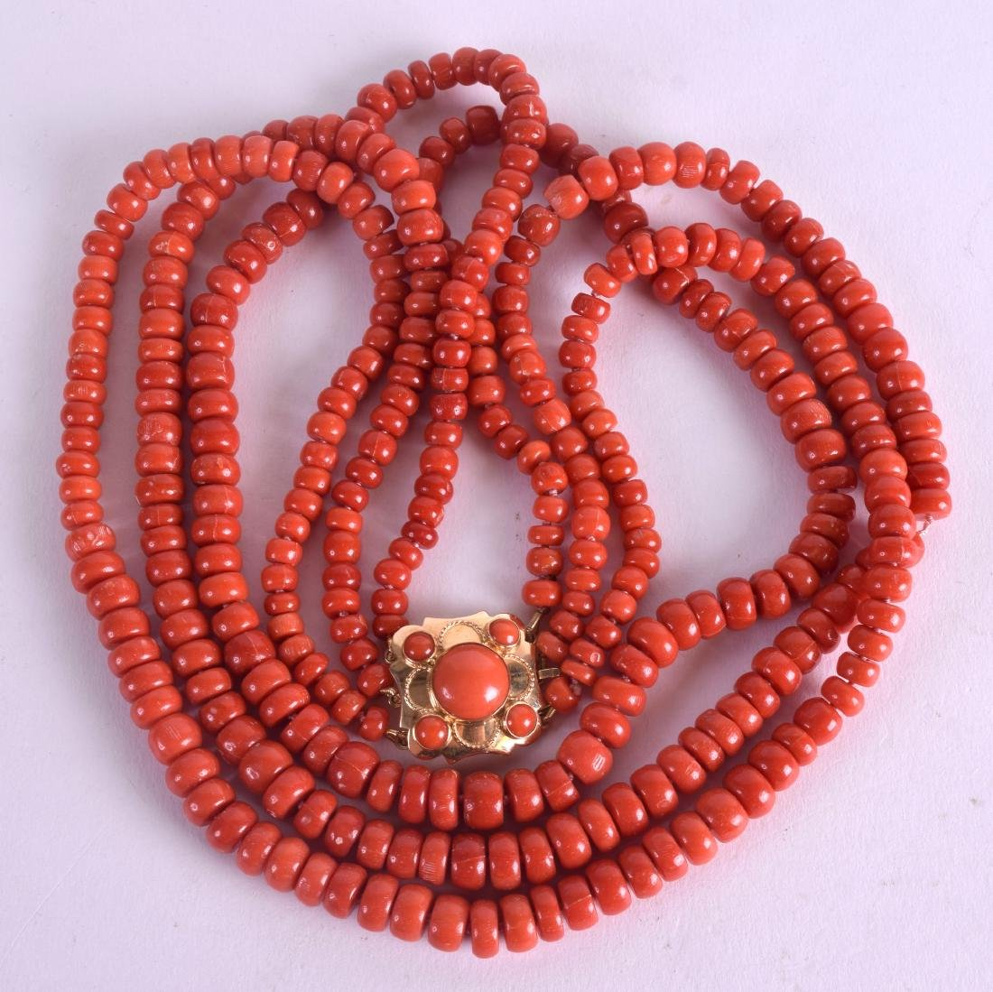 AN 18CT GOLD AND RED CORAL NECKLACE with coral inset
