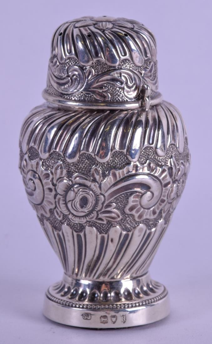 A LATE VICTORIAN EMBOSSED SILVER PEPPER POT. London