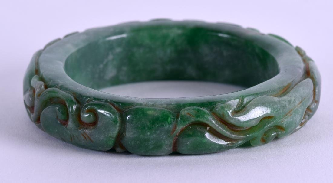 A CARVED GREEN JADE BANGLE. 8 cm wide.