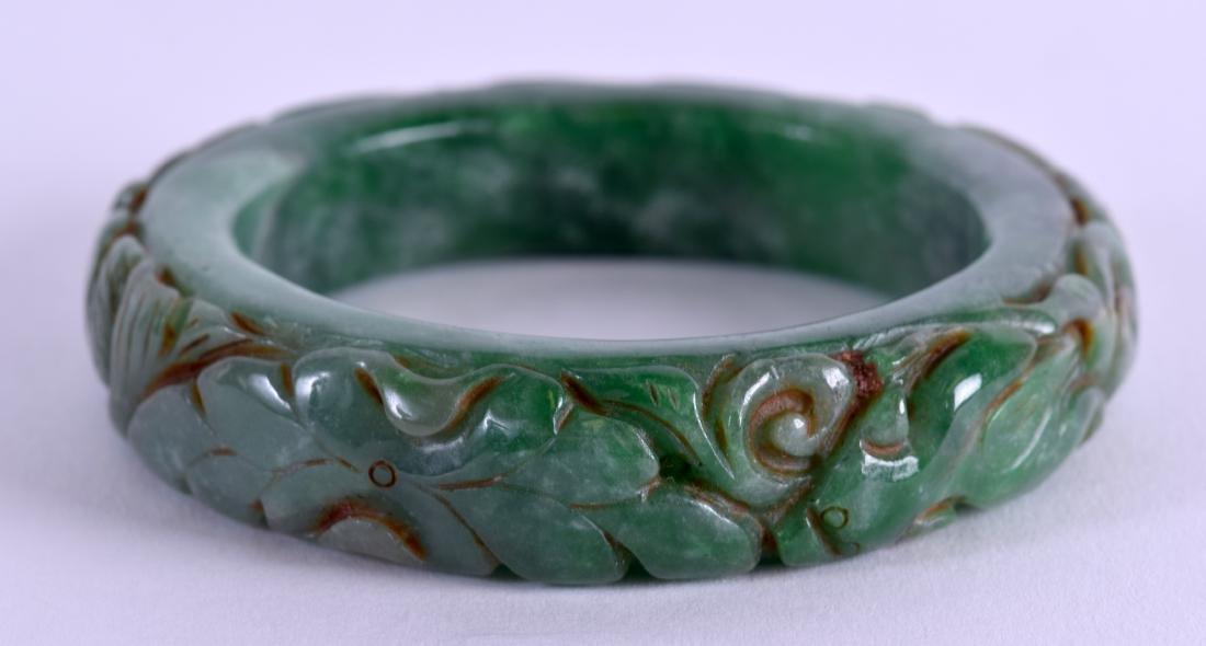 A CARVED GREEN JADE BANGLE. 8 cm wide. - 2