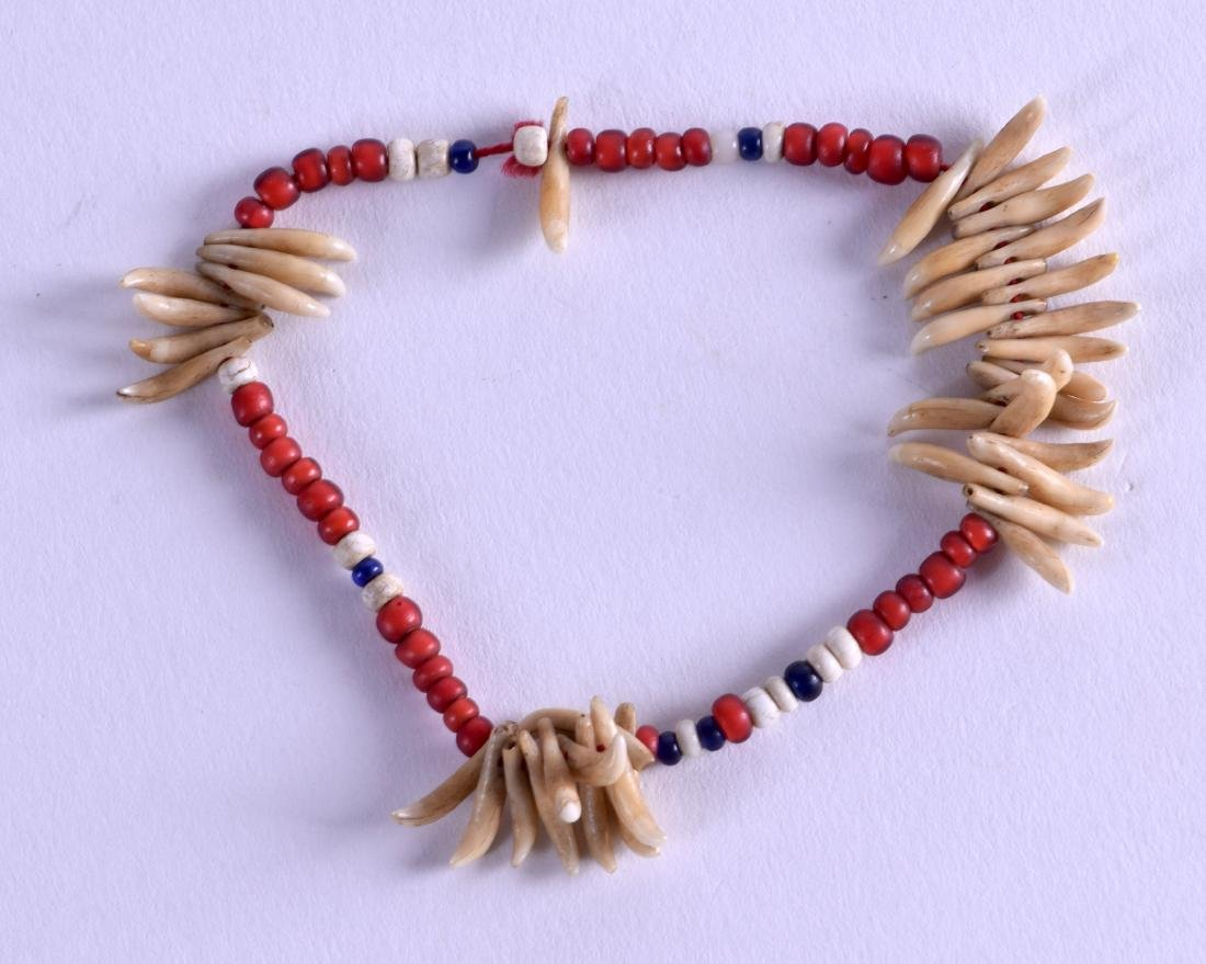 AN EARLY 20TH CENTURY TRIBAL CORAL AND TOOTH BRACELET.