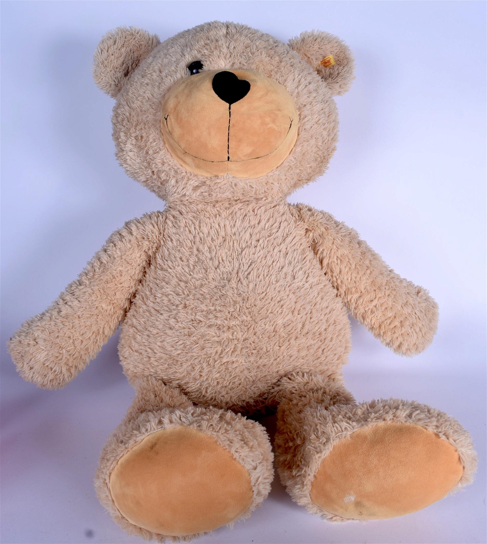 A HUGE STEIFF TEDDY BEAR, bearing button and label to