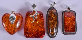 FOUR SILVER AND AMBER PENDANTS. (4)