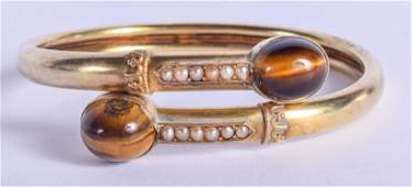 A VICTORIAN 15CT GOLD PEARL AND TIGERS EYE BANGLE 14