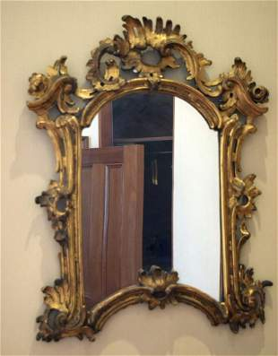 AN ANTIQUE CONTINENTAL GILTWOOD SCROLLING MIRROR with