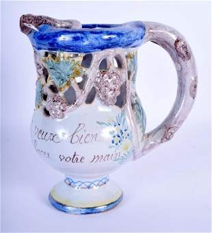 A FRENCH FAIENCE TIN GLAZED PUZZLE JUG. 17 cm high.
