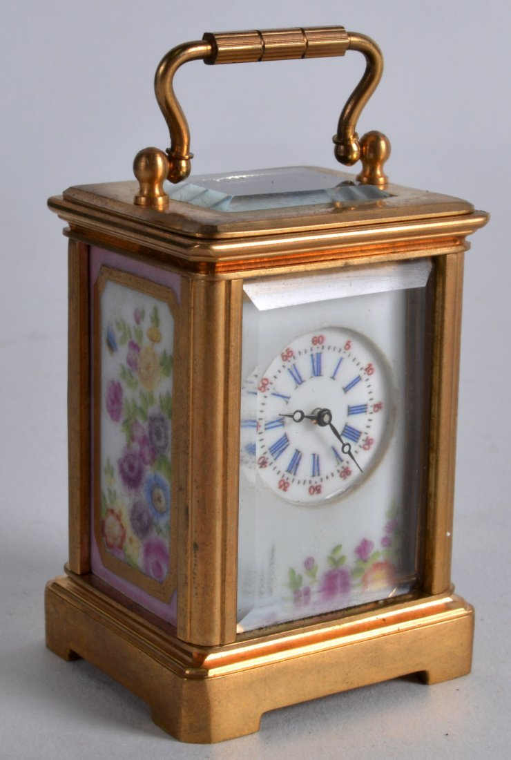 A MINIATURE BRASS CARRIAGE CLOCK inset with painted