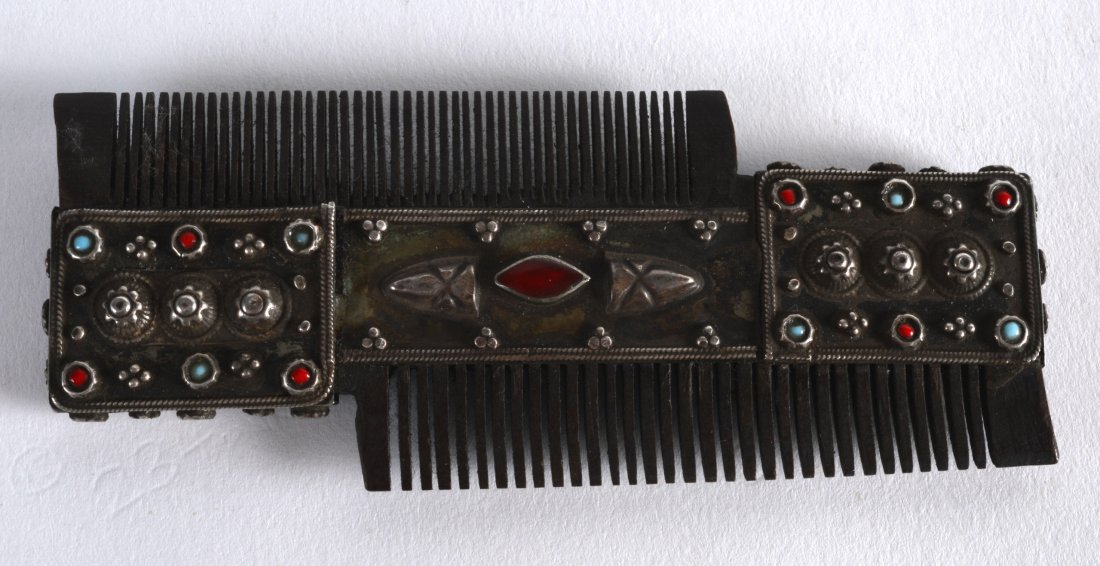 A 19TH CENTURY TIBETAN WHITE METAL AND CORAL COMB