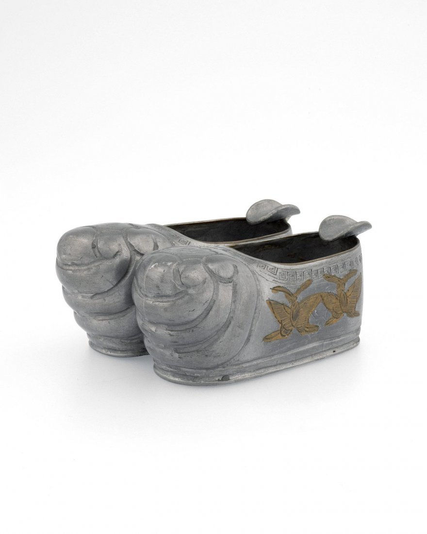 A SMALL PEWTER ASHTRAY CARVED IN THE SHAPE OF FOOT-BOUN