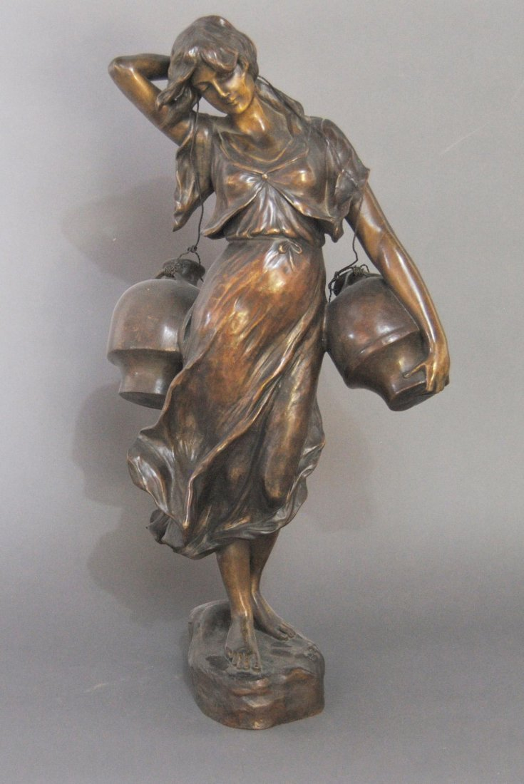A finely cast bronze of a woman carrying two water jugs