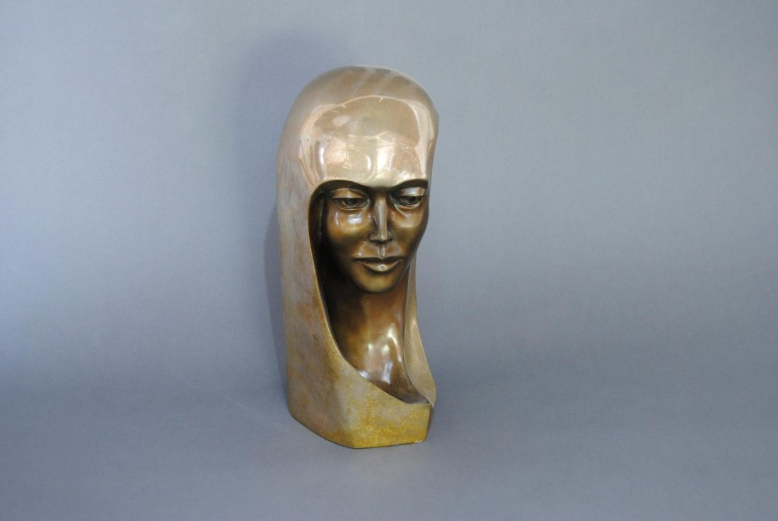 A BRONZE HEAD OF A WOMAN WITH LONG HAIR AND A HIGHLY-PO