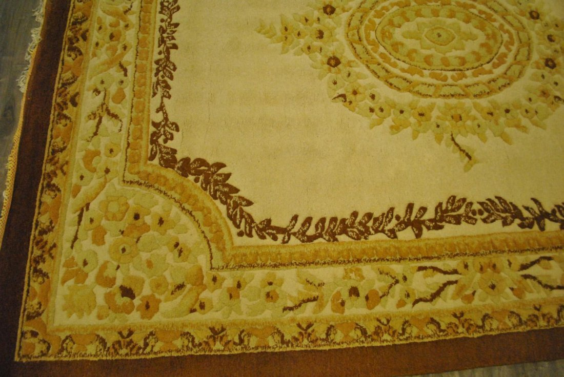 A YELLOW AND BROWN HAND-KNOTTED INDIAN CARPET,