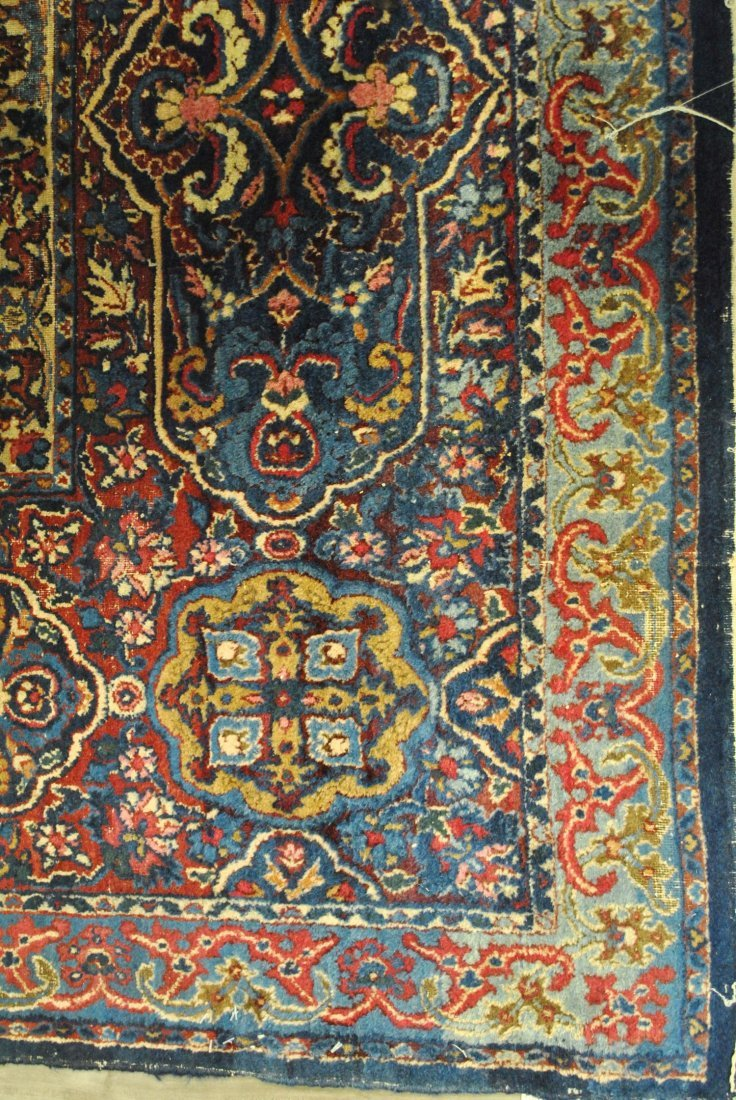 A BLUE AND RED HAND-KNOTTED ANTIQUE KERMAN,
