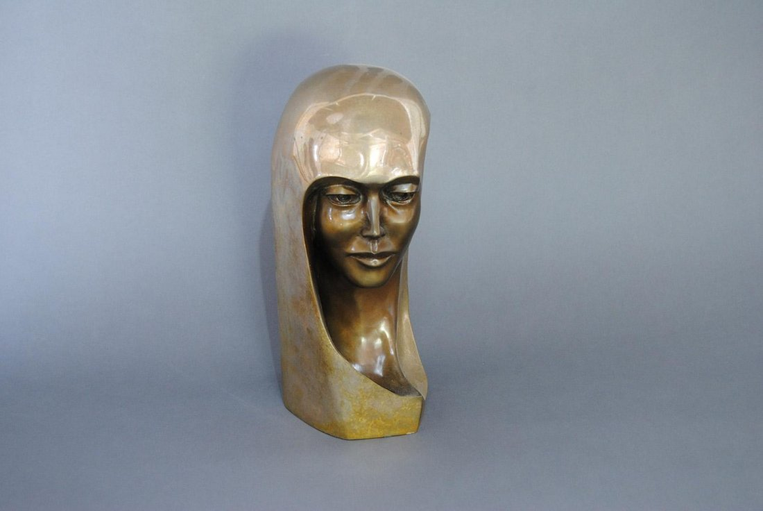 A BRONZE HEAD OF A WOMAN WITH LONG HAIR AND A HIGHLY-P