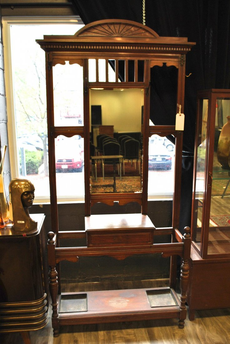 A tall oak vanity with mirror, surface area and metal