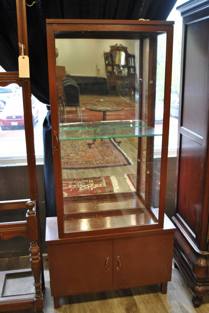 A Mirrored Backend Cabinet With Two Glass Shelves,