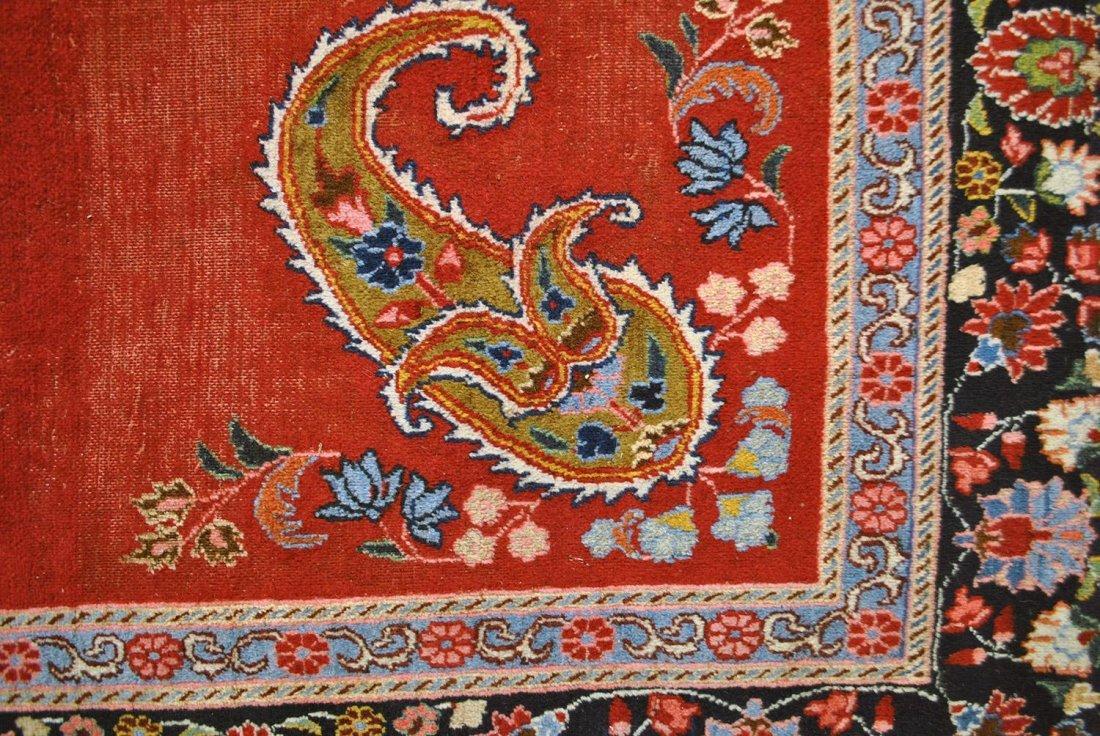 A STRIKING ANTIQUE PERSIAN KIRMAN IN RED, BLUE, BLACK,