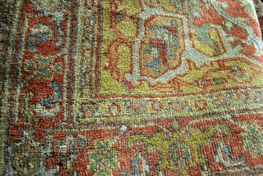 A SMALL GREEN, RED, AND BEIGE PERSIAN RUG WITH