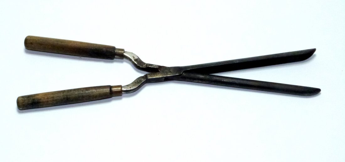 Old metal curling tongs or hair iron.