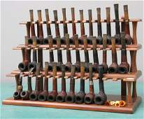 1274: Thirty-three pipes in three-tier display shelf, b