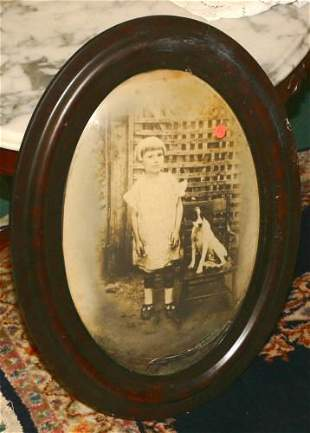 Oval frame/print, grained, girl seated with dog.
