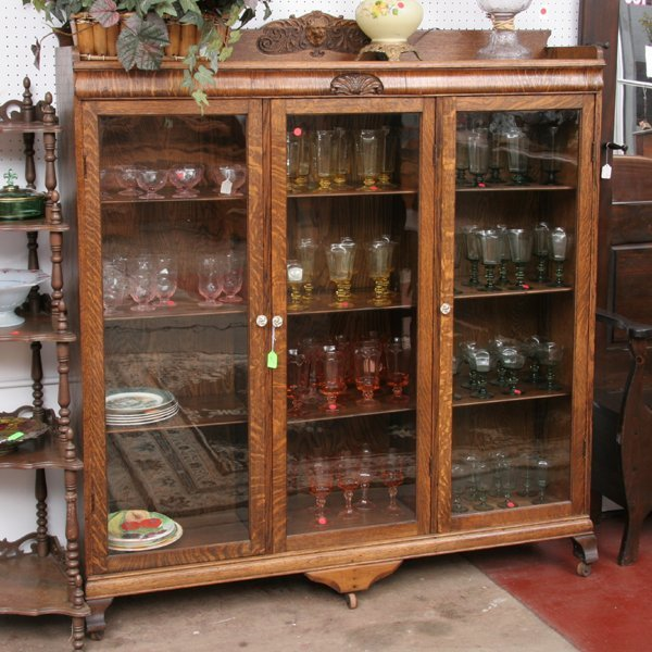 1014: C1900 triple door bookcase, tiger oak, carved bac