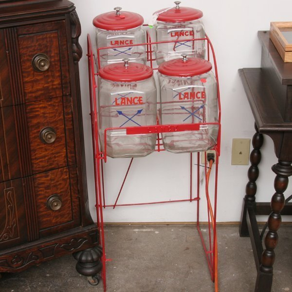 1054: Old Lance advertising stand, four glass jars with