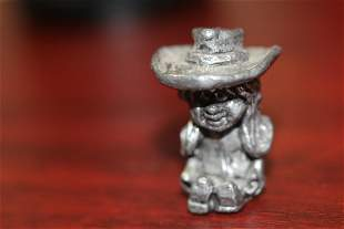 A Small Pewter Cow Girl