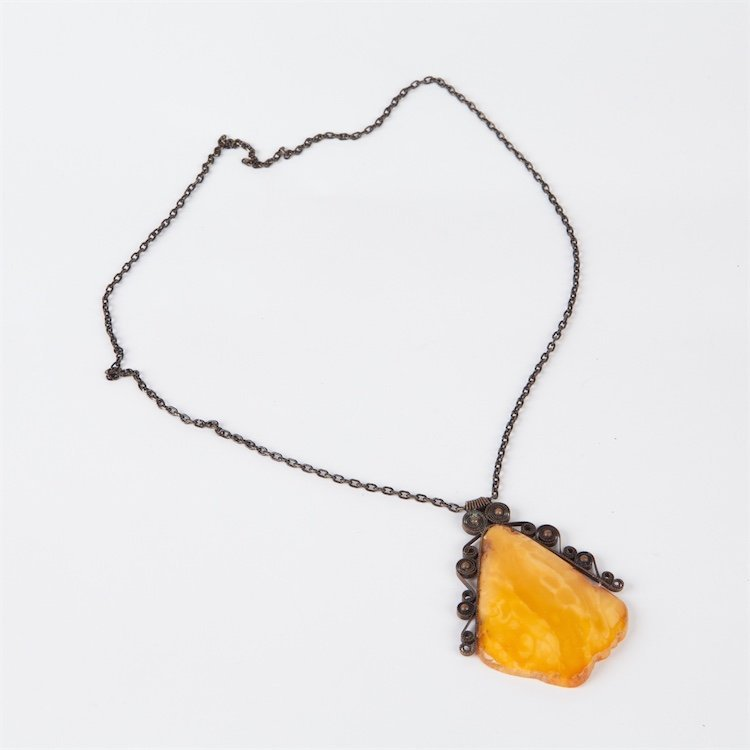 Antique amber pendant on metal chain.