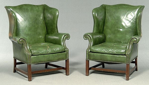 669: Pair green leather wing chairs,