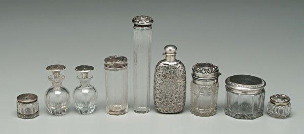 736: Nine sterling and glass bottles,