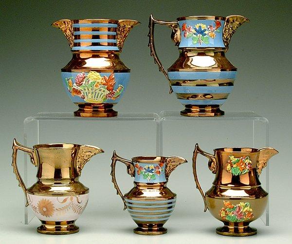 609: Five mask-spout copper luster jugs,