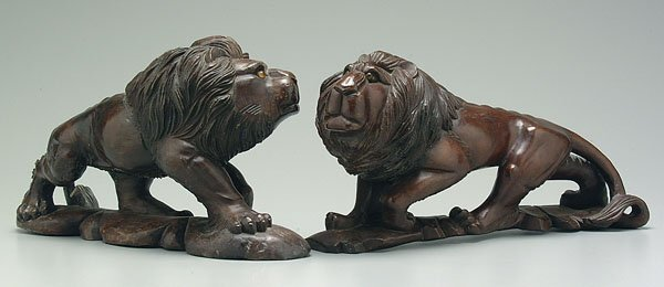 12: Two similar carved wood lions,