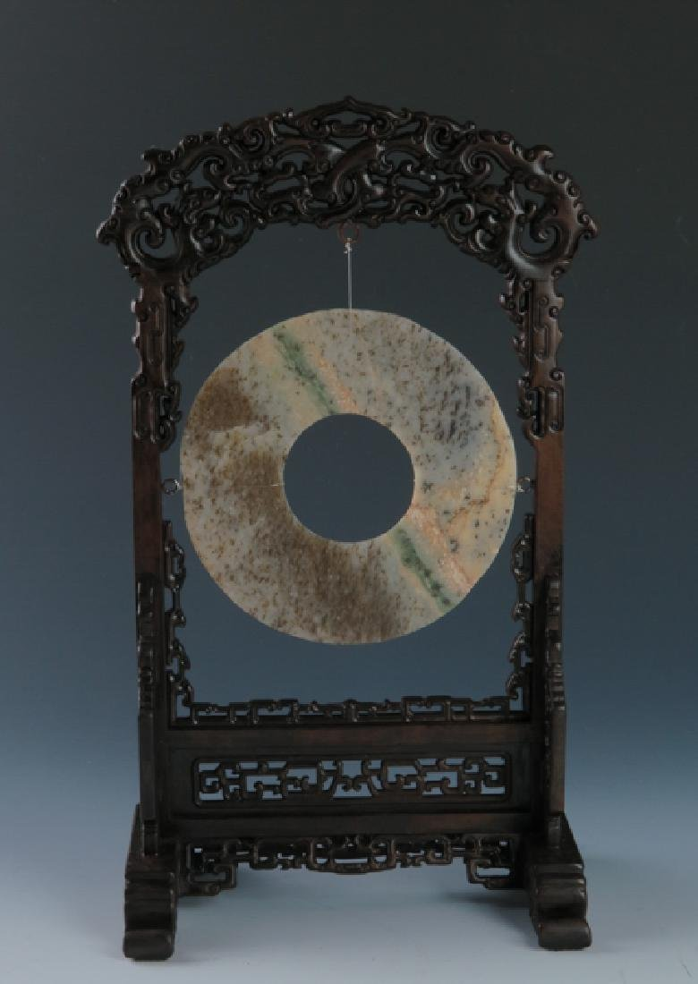 A jade disc with rose wood stand