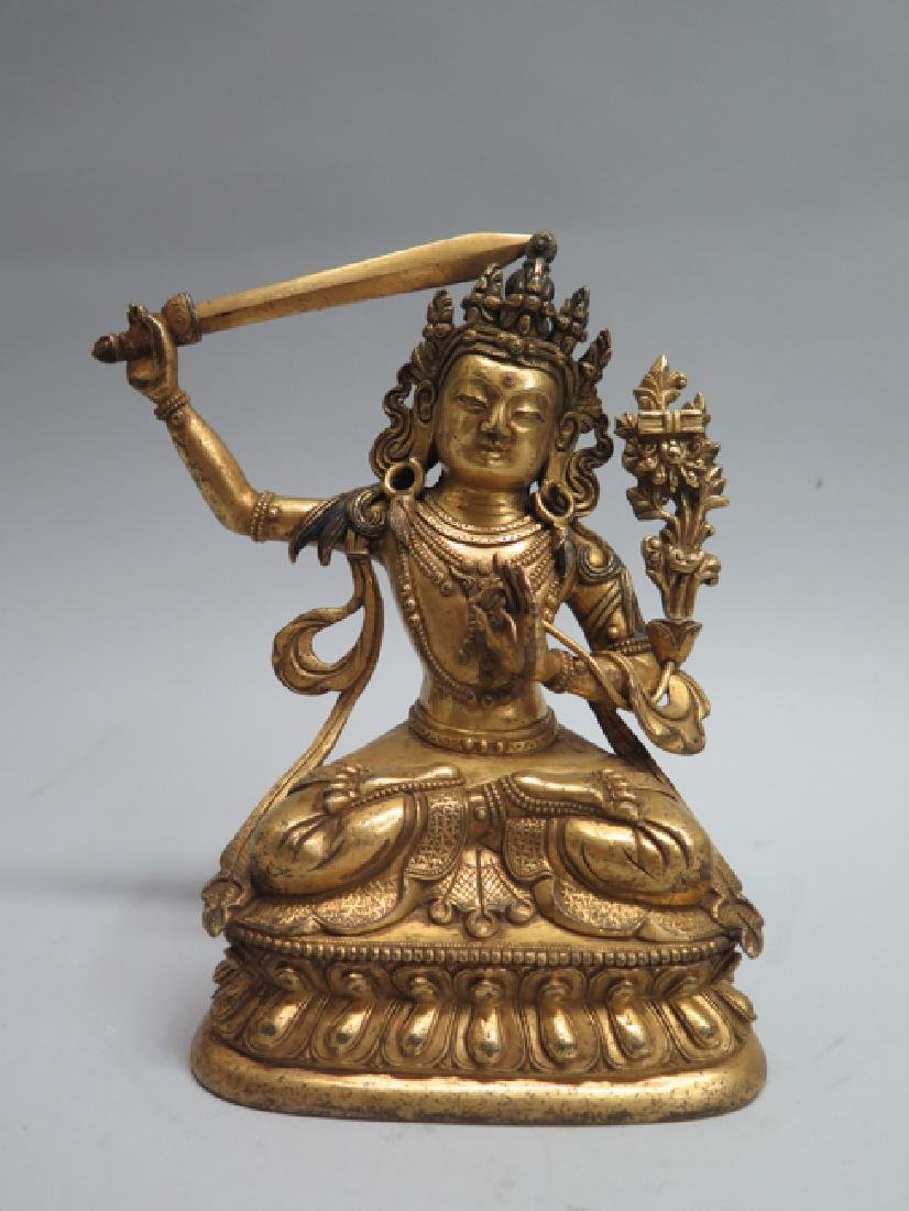A gilt bronze figure of Manjushri