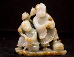 A CARVED CELADON JADE FIGURE OF IMMORTALS