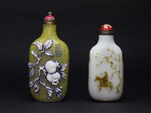 Two glasses overlay decorated snuff bottles.