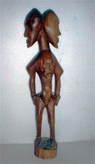 Wood carving of two conjoined heads