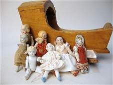 73: Wooden Cradle with Seven Small Dolls