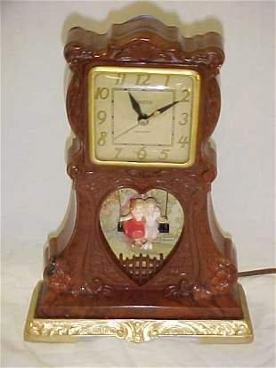 24: Vintage electric United music clock couple on swing