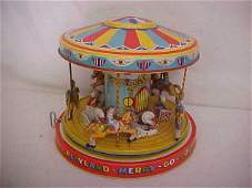 56: Early tin litho wind up playland merry go round