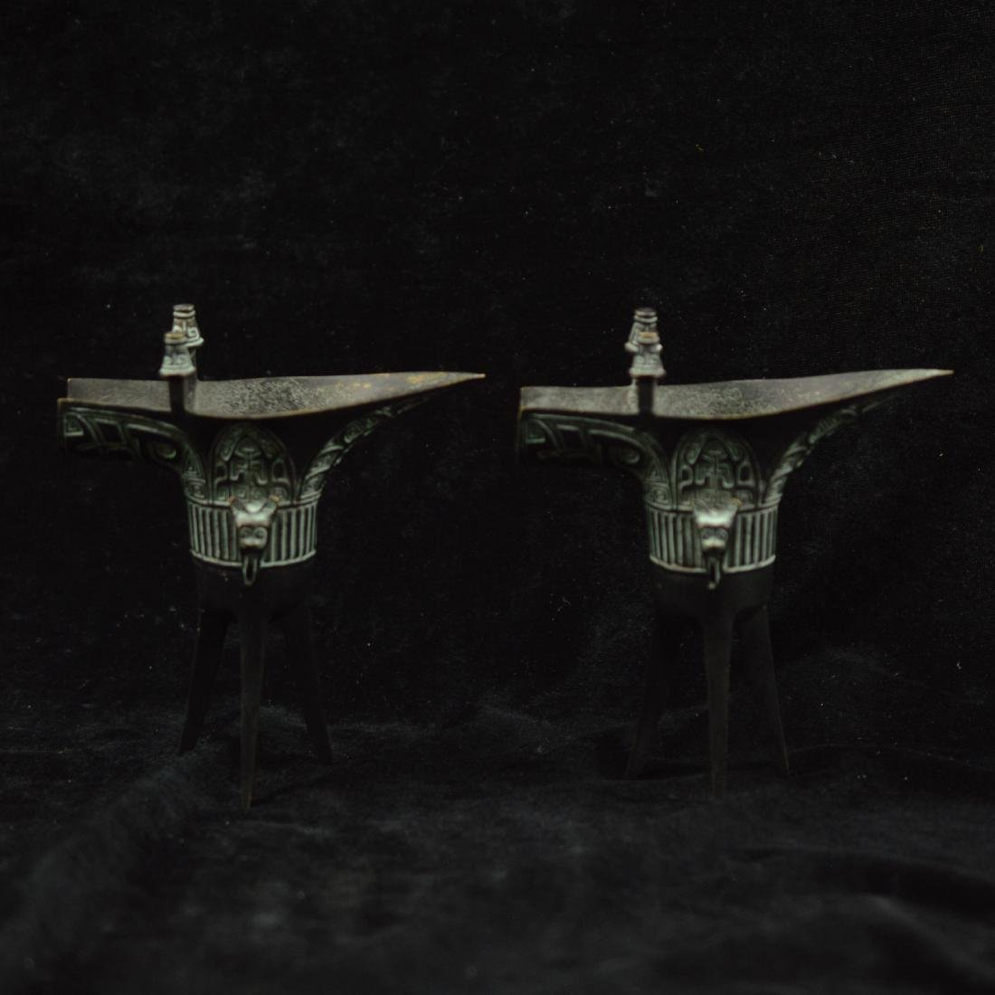 pair of old bronze tripod cups