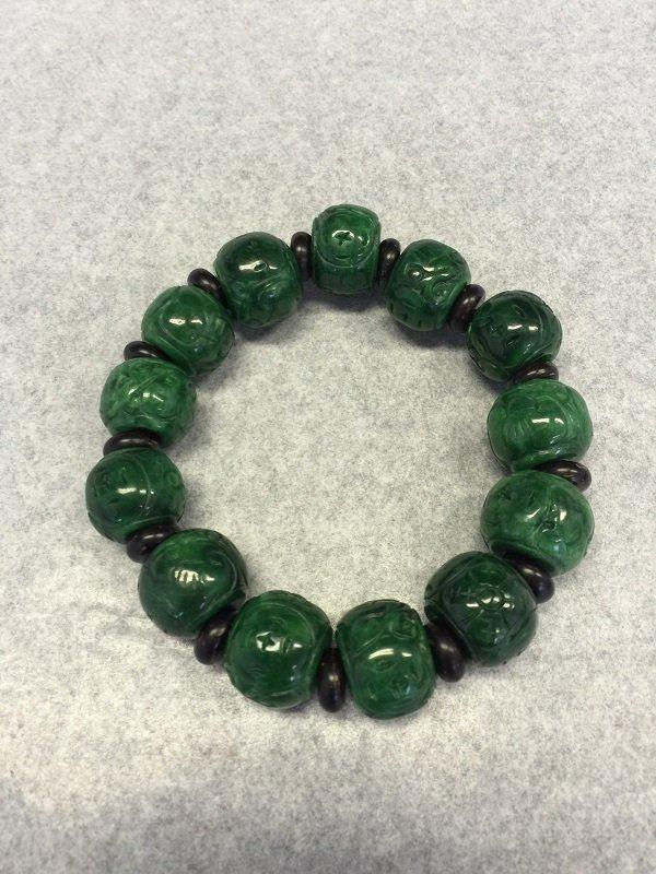 A Finely Carved Spinach Jadeite Bead Bracelet