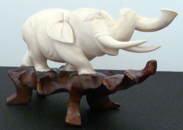 211: CARVED IVORY ELEPHANT ON TEAKWOOD BASE