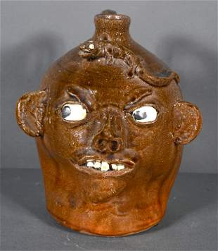 Chester Hewell. Traditional Glaze Face Jug with Lizard.