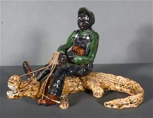 Man Riding Alligator Ceramic Sculpture.