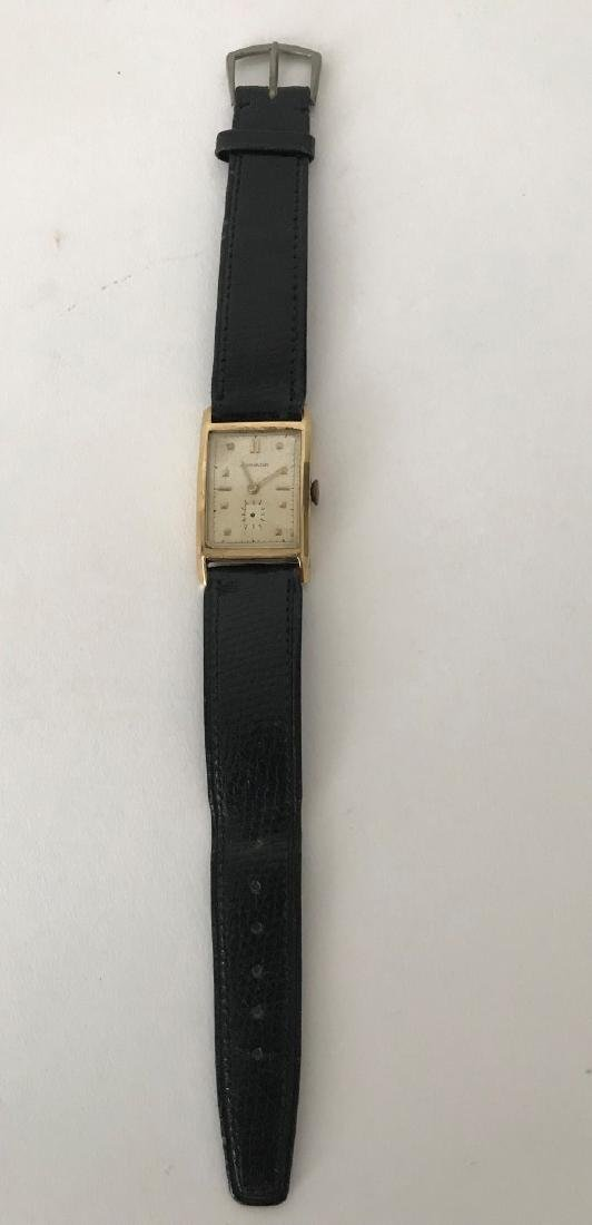 Men's 14K Yellow Gold Movado Watch with leather strap.