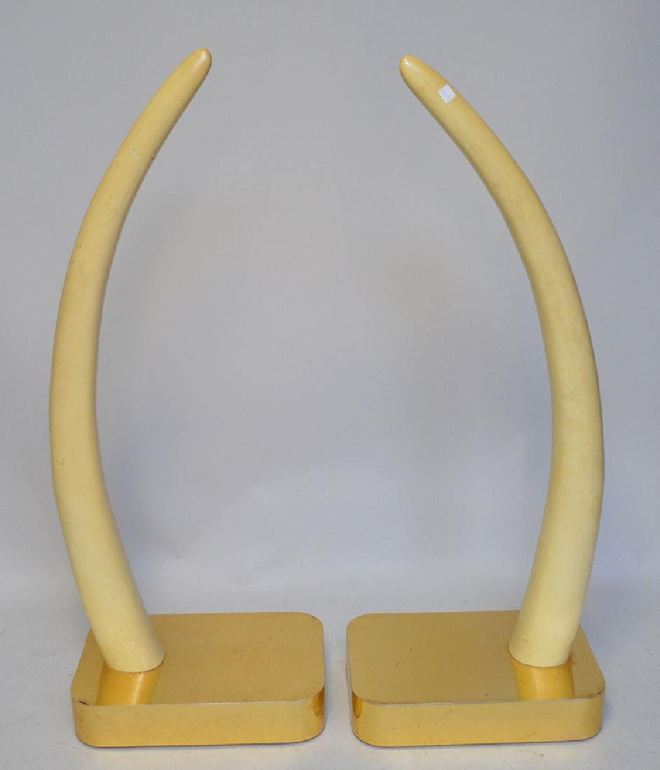 Pair ivory type elephant tusks on brass platform bases,